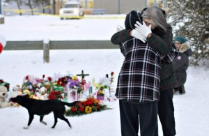 Residents console each other at the memorial near the La Loche Community School in La Loche, Canada, Sunday, Jan. 24, 2016. A Friday shooting left four people dead, the Canadian Press reports. (Jason Franson/The Canadian Press via AP) MANDATORY CREDIT